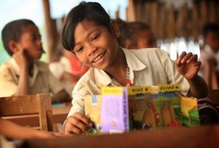 A girl smiles in a class in Ensino Basico Filial Nuno-Sacari School in Ermera District, Timor Leste