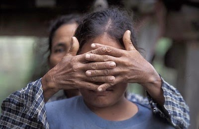 A mother covers her daughter's face to protect her identity. Her daughter was trafficked at the age of 16