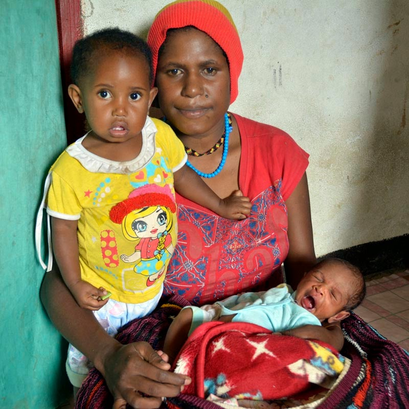 Neli with her daughter and newborn boy in their communal home