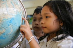 In the Philippines, a school girl points out her country on a globe.