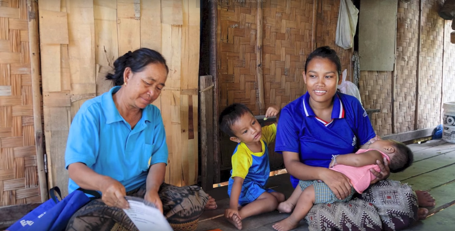 Pa, a mother of two, is shown information about breastfeeding and healthy eating by a Lao Women's Union volunteer