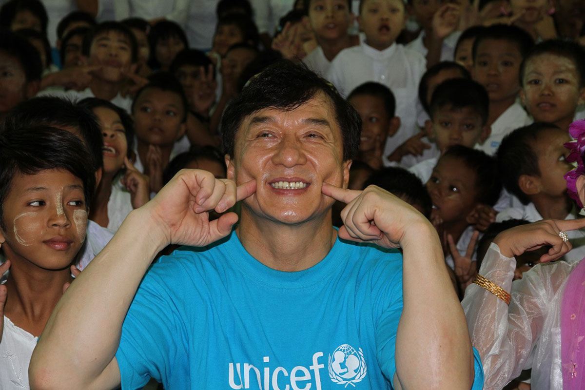 """Jackie together with children from the School for Deaf in Mandalay showing his name in sign language """"Jackie Chan"""""""