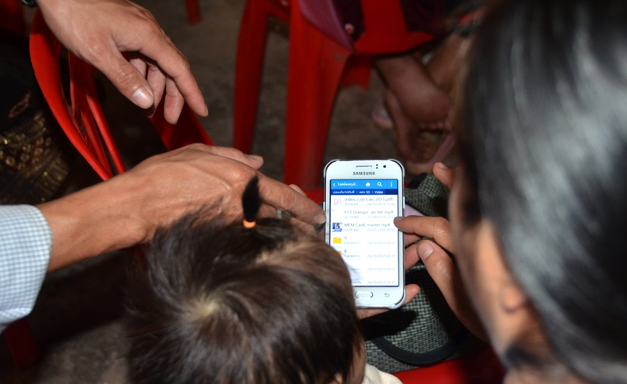 A mother holds her daughter while receiving instructions on how to access the information the SD cards.