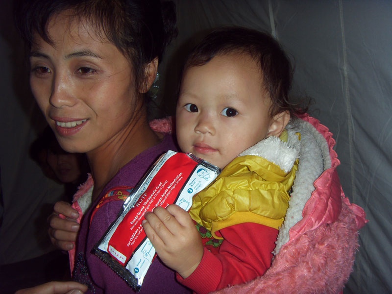 A baby holds plump-nut, used to treat malnourished children. Clinics expect cases to continue rising after the floods.