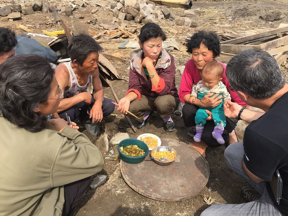A Korean family eat a meal in the rubble of their destroyed house, while talking with UNICEF Deputy Representative Murat Sahin (right)