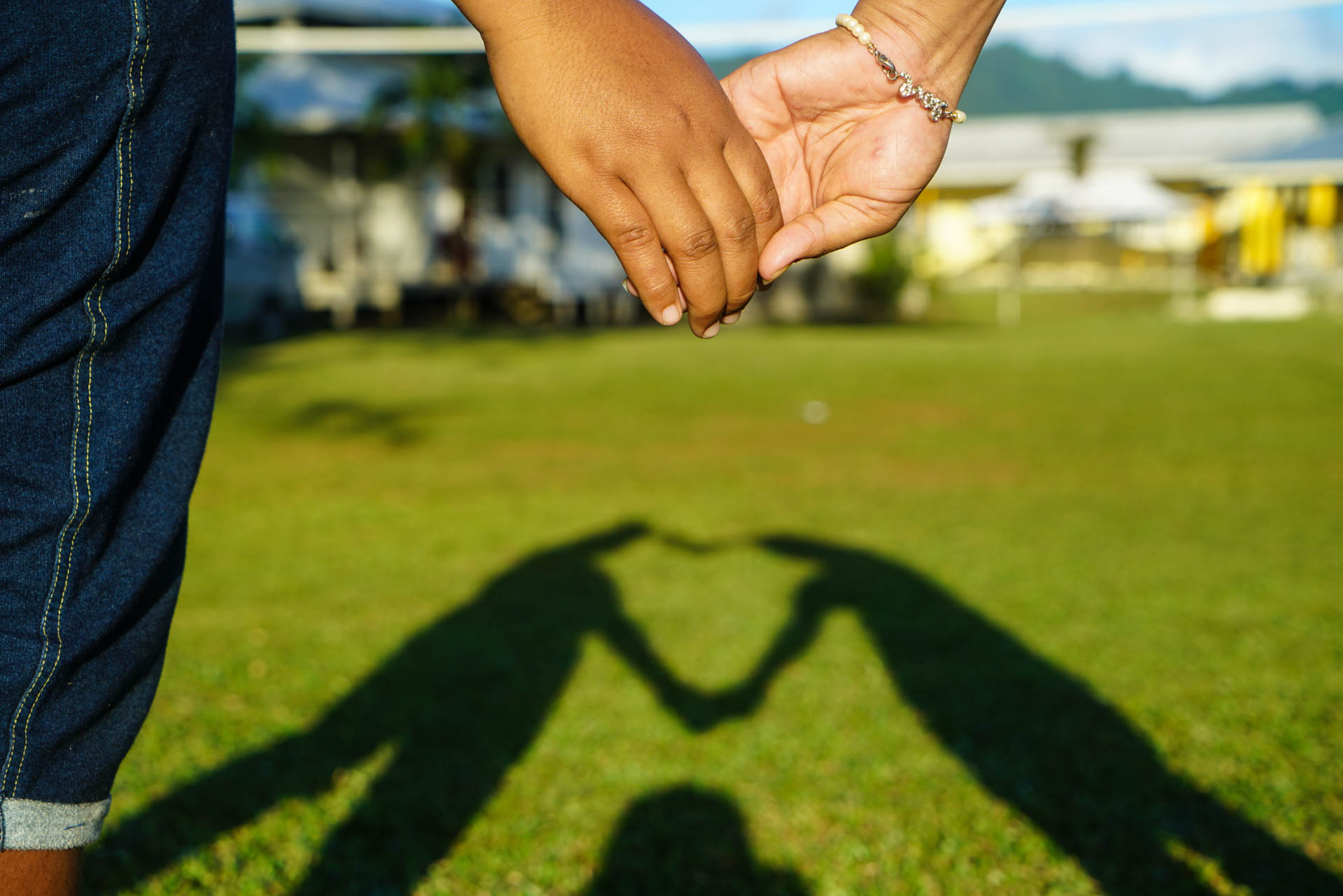 Two survivors of violence hold hands to form a heart at the Campus of Hope