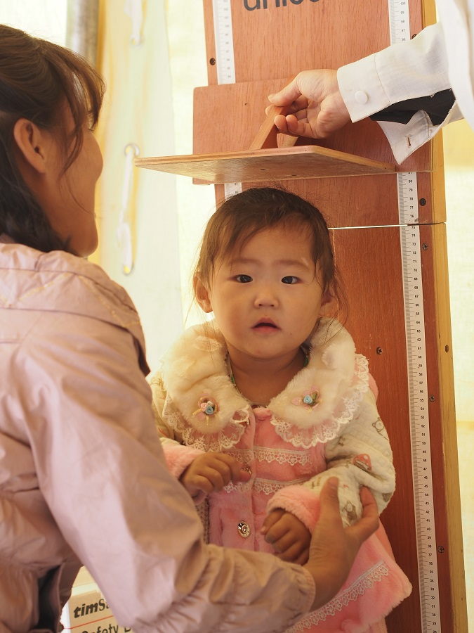 Sim Hye Sun's daughter is measured in the health clinic. She was diagnosed as being malnourished, which is increasingly common since the floods.