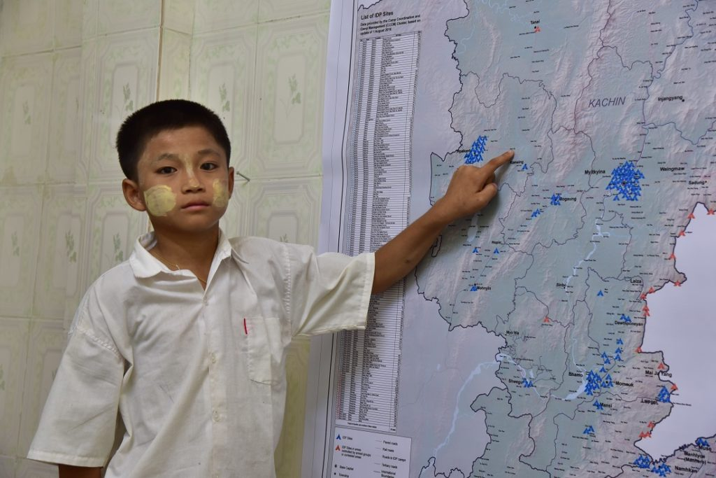Seng points to the location of his village, where the attack happened, on a map of Kachin State