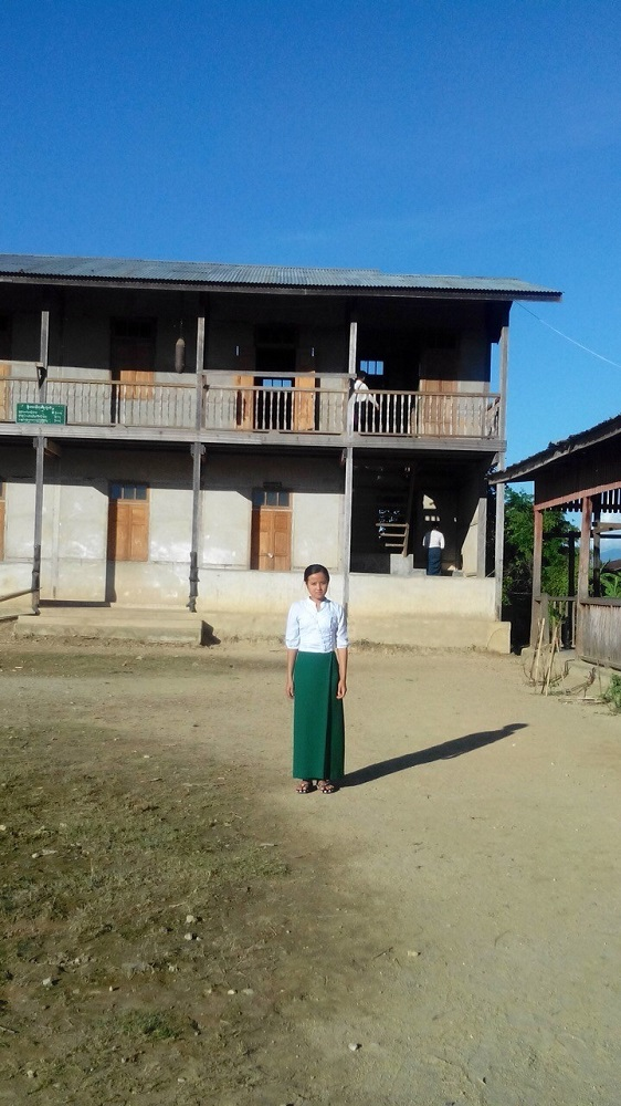 Mya stands outside Nam Ya Middle School, where she and Seng were injured in an attack