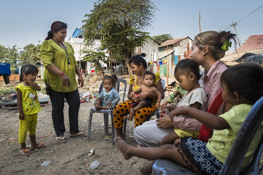 Health volunteer Sokly Ye explains to mothers the importance of vaccinations for child health in Svay Pak village, Cambodia.
