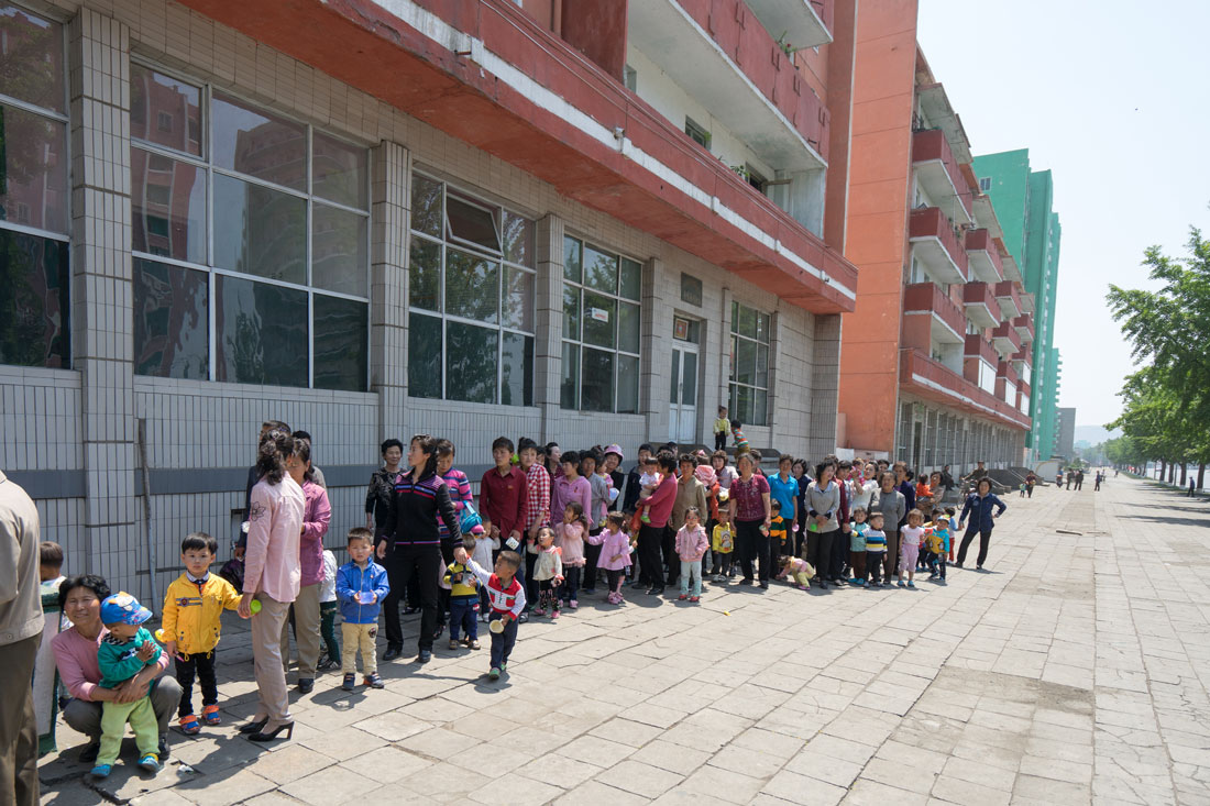 Parents and children queue outside the district hospital in Sariwon City