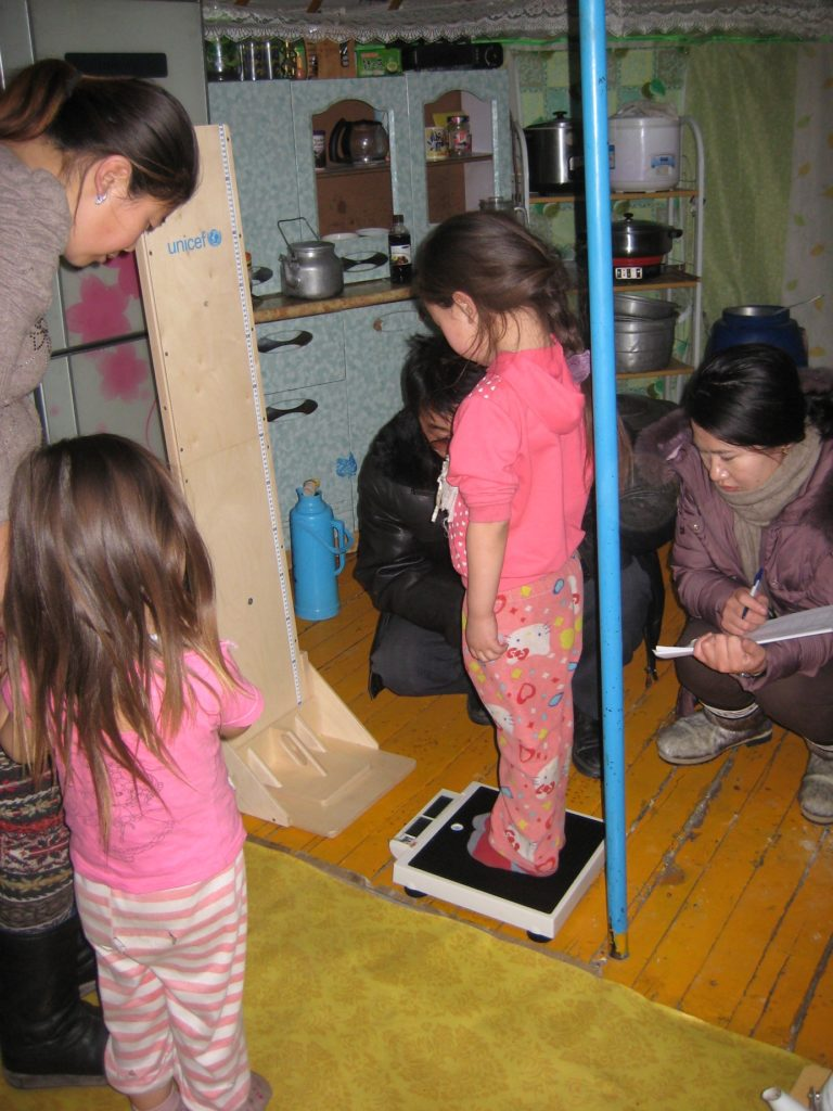 Enumerators measure the height and weight of children in a Mongolian household.
