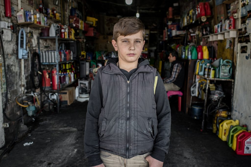 A 14 year old Syrian refugee from Kobani, stands for a portrait at the car repair shop where he works in Erbil in the Kurdistan region of Iraq., 2016.