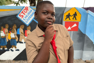 Photo of a schoolboy posing against the wall of Hazard Primary School in Clarendon carrying a road safety message for the X Marks The Spot campaign