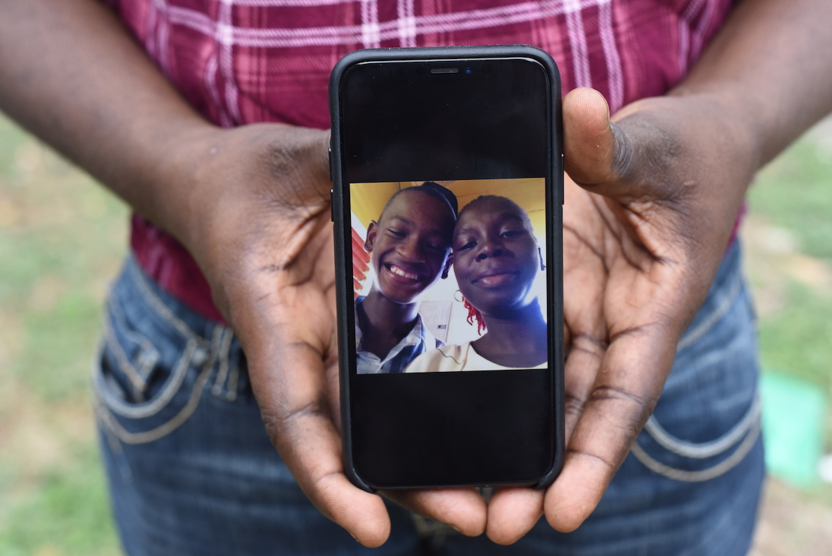 Photograph of Kenisha Williamson holding a photo of her son Adrian, at a recent parent support group meeting held by the Jamaica Autism Support Association (JASA).