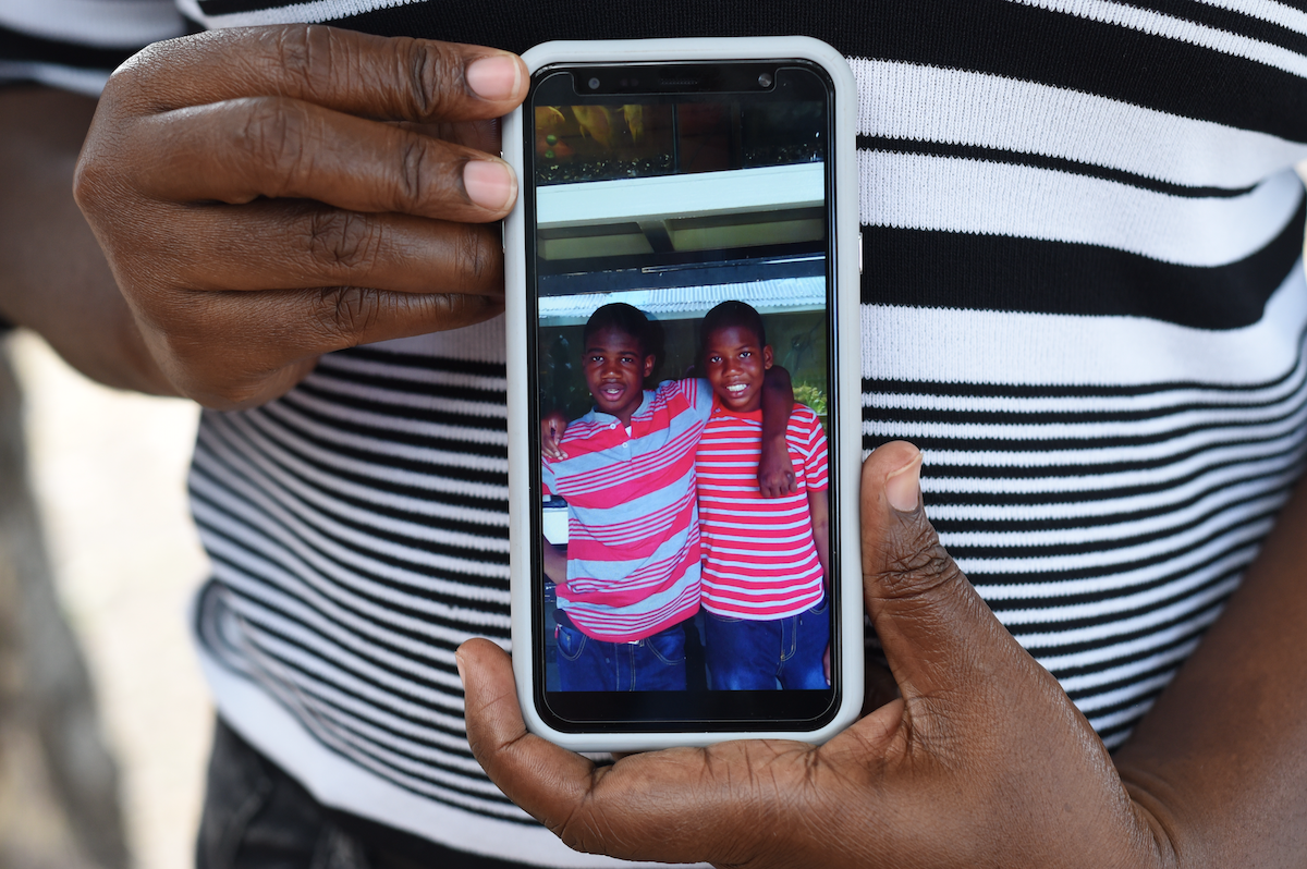 Parent Nicola Francis holding a photograph of her twin sons Tegan and Taigan at a recent parent support group meeting held by the Jamaica Autism Support Association (JASA).