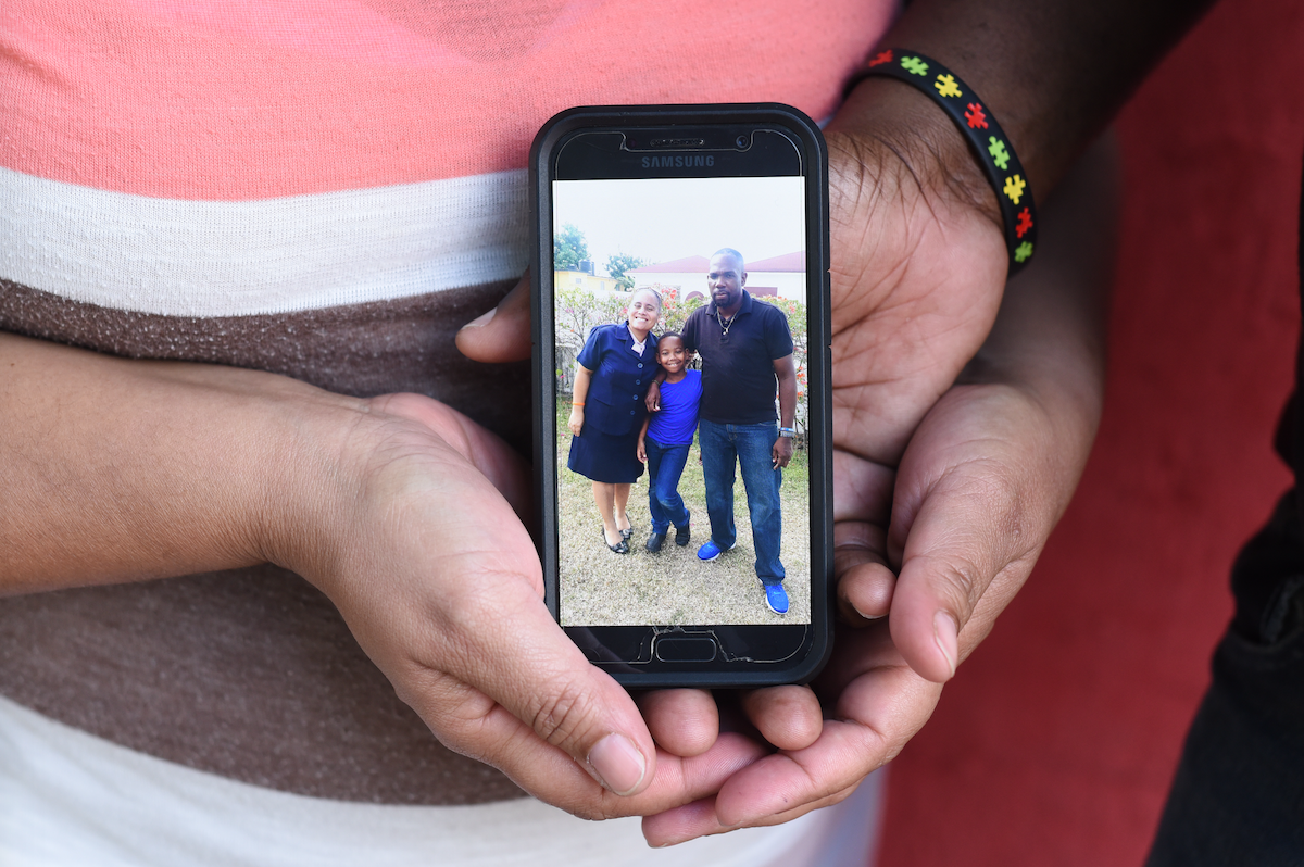 Lisa and Stephen Henderson holding a photograph of their son Sean, at a recent parent support group meeting held by the Jamaica Autism Support Association (JASA).