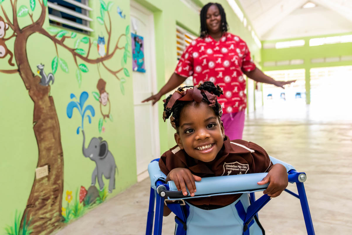 Photograph of Nadine Bowen, a teacher at Early Stimulation Plus in Rockfort, eastern Kingston together with one of her students.