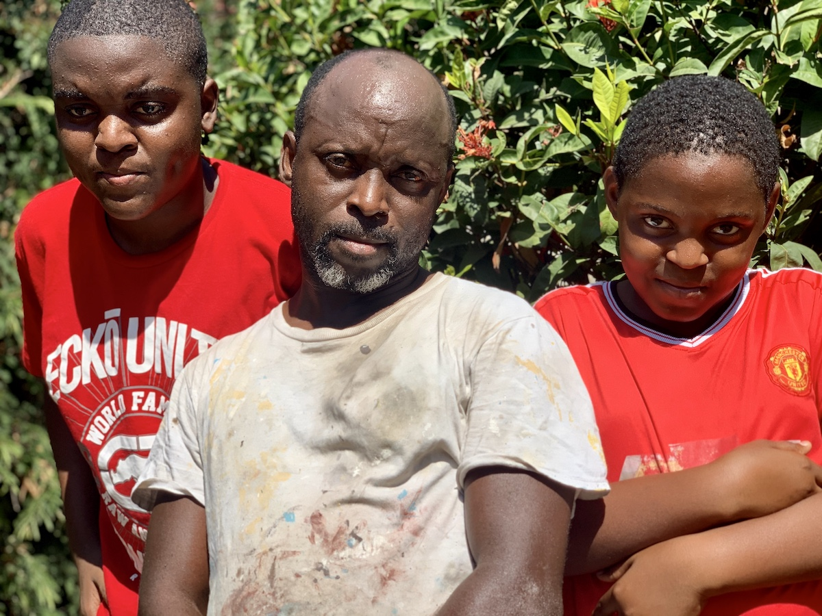 Photograph of Father Ian 'Cowfoot' Salmon together with his two sons Jevontae, aged 16 (left) and Devontae, aged 13 in their community of Mountain View, St Andrew.