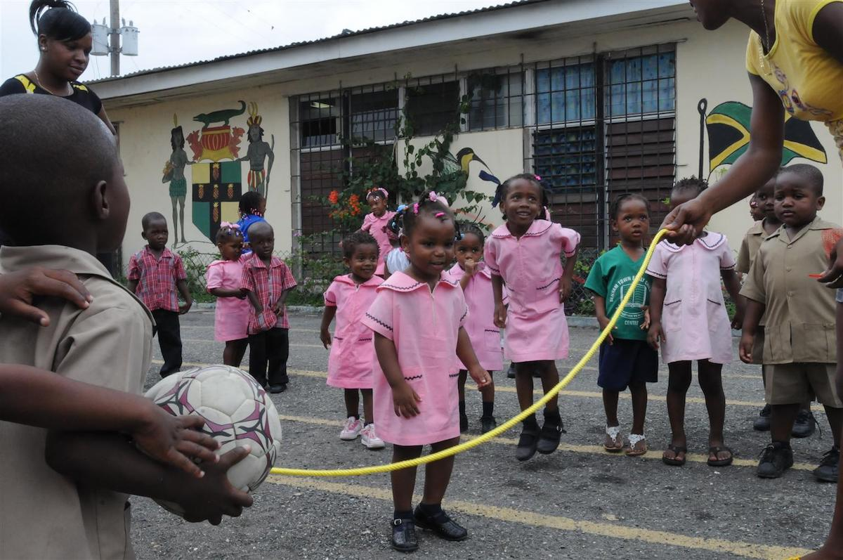 A girl learns to jump rope at the UNICEF-supported Denham Town Basic School in the Denham Town community in the parish of Kingston and St. Andrew. Nearby, a boy holds a football. Many poor families cannot afford pre-school fees, books or uniforms, so their children do not attend school regularly. In May 2008 in Jamaica, children continue to suffer hardships wrought by a fragile economy, pervasive violence and poverty. Violence in the home, in schools and in communities continues to affect children, who comprise more than 37 per cent of the population of 2.7 million. Girls are vulnerable to sexual abuse, while boys are often the victims of assault. In 2007, more than 1,500 people were murdered (equal to more than four people a day), including an estimated 100 children. In a recent national survey, 60 per cent of 9 to 17-year-old children reported that a family member had been a victim of violence and 37 percent has a family member who had been killed. Only 28 per cent of children thought their community was safe. Gang activity has increased, with gang members enlisting children to conceal their weapons. Children's rights to education and leisure activities have been compromised by unrelenting levels of crime, forcing school closures due to civil disturbances. UNICEF supports violence prevention, reduction and mitigation programmes and other integrated care and protection services for vulnerable children and young people, including: child-friendly safe spaces in violence-prone communities; mediation, conflict management, peace promotion and life-skills training for adolescents in inner-city communities; improved access to psychosocial services for children and families; remedial education; skills development and counselling; income-generating activities; and rehabilitation and reintegration programmes for out of school children, including those living or working on the streets. UNICEF also supports quality education and early childhood development. The latter programme also aims to improve the quality and accessibility of health services for younger children and their mothers.