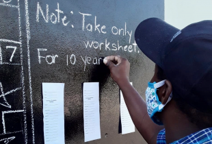 Teacher Taneka McKoy-Phipps writing another day's schoolwork on a community blackboard in Kingston.
