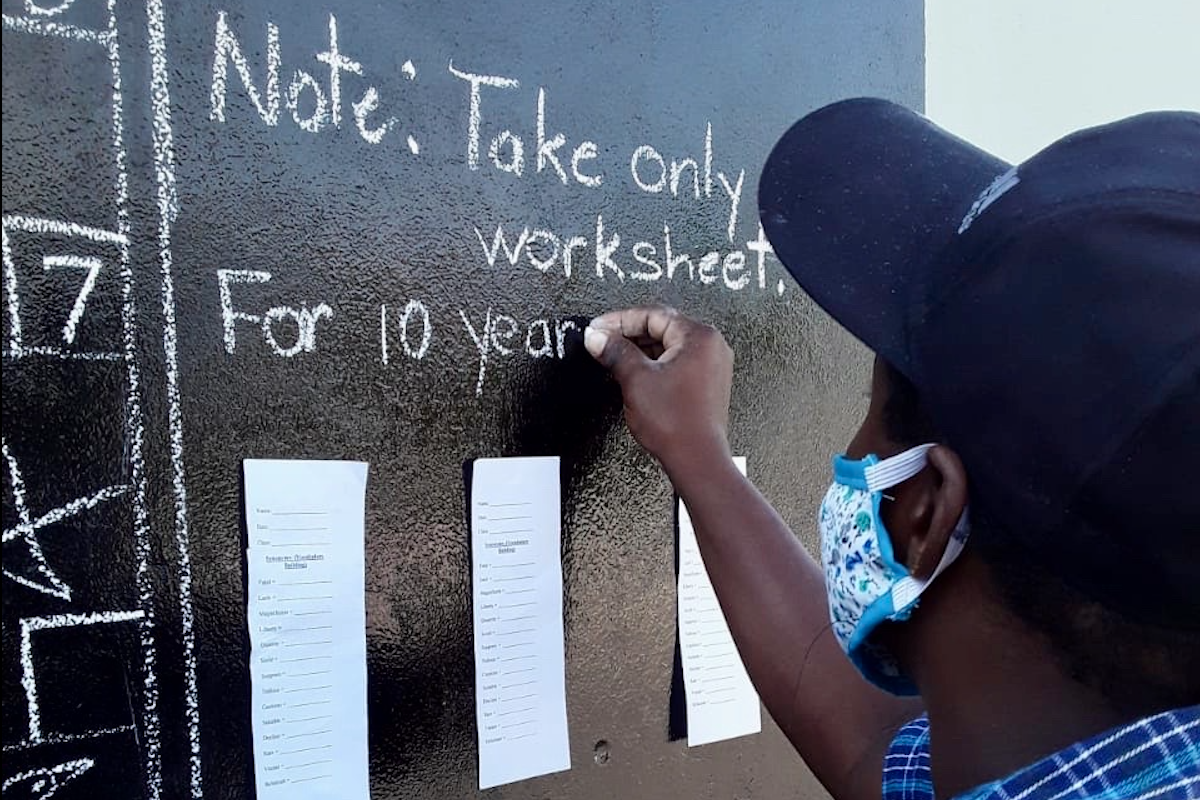 Teacher Taneka Mckoy Phipps writing another day's schoolwork on a community blackboard in Kingston.