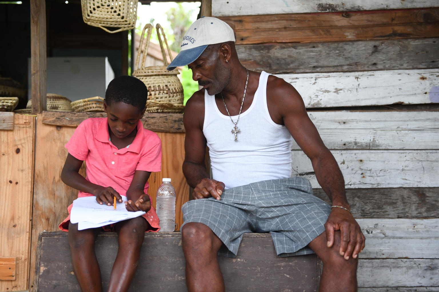Joel Young a student of Little Bay Primary and Infant school with his father Wayne Young a fisherman. going through the weeks lessons. The school is located in Little Bay, a mainly fishing community located in the parish of Westmoreland, the western end of the island of Jamaica on Monday, September 7, 2020. Little bay primary and infant schools is one of the schools which participated in an online course supported by UNICEF – designed to help schools adjust to the new reality as finding its own innovative way to keep children learning since schools were closed in March children have faced obstacles to learning – whether it be access to the internet, or indeed whether their teachers have the necessary skills to provide distance learning. The Virtual Instructional Leadership (VIL) course supported by UNICEF and offered by the National College for Educational Leadership (NCEL) aims to give school leaders the necessary skills to keep children learning despite the pandemic.