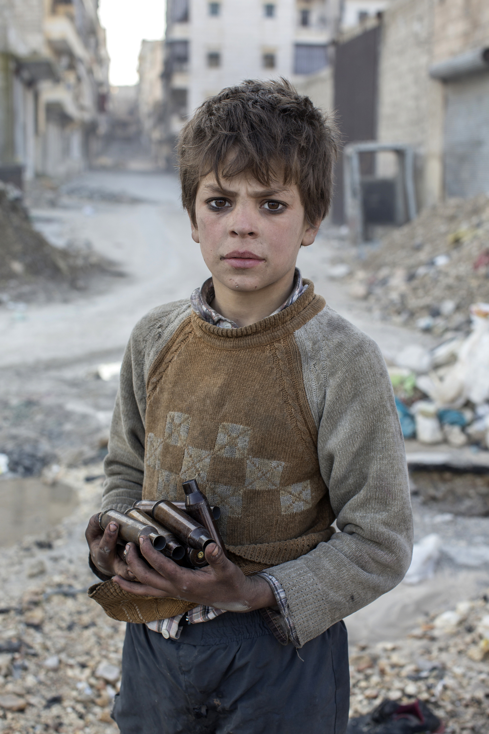 Nine year old Alladin collects used ammunition to sell as metal in Aleppo, Syria.
