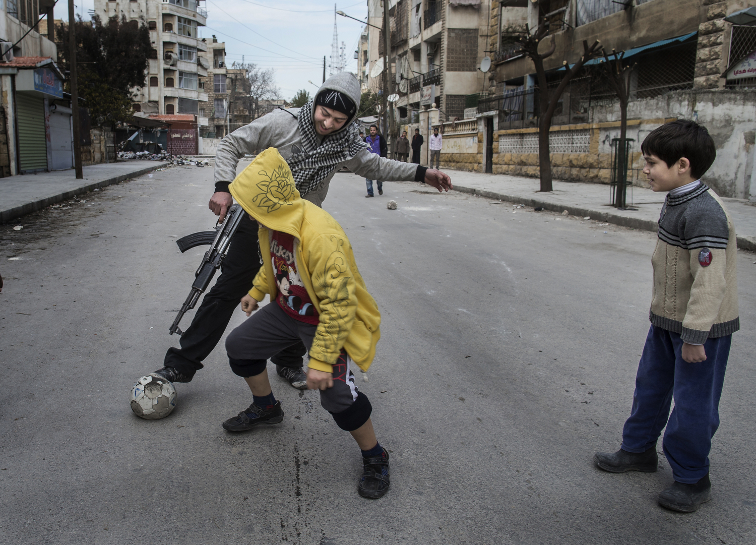 A Free Syrian Army fighter plays football with children in the Saif al-Dawlah neighborhood of Aleppo.