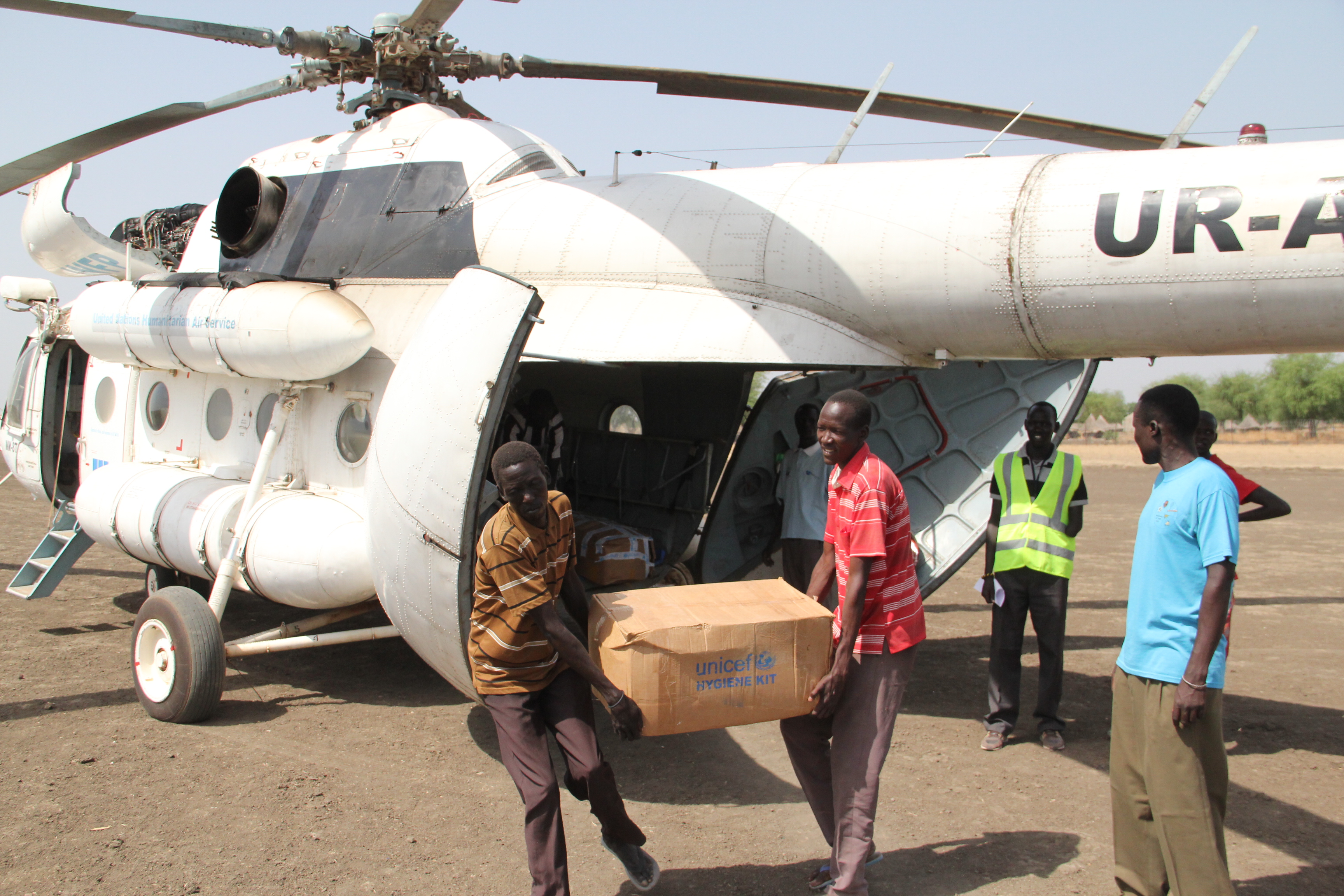 Two of the more than 100 volunteers in Akobo, South Sudan, helping to unload hundreds of tons of life-saving UNICEF supplies and clear land for emergency air drops.