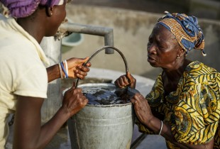 A young woman helps an elderly woman lift a bucket of water A young woman helps an elderly woman lift a bucket of water she just filled from a UNICEF-sponsored hand pump in the village of Mano Njaigbla, Kenema district, Sierra Leone.