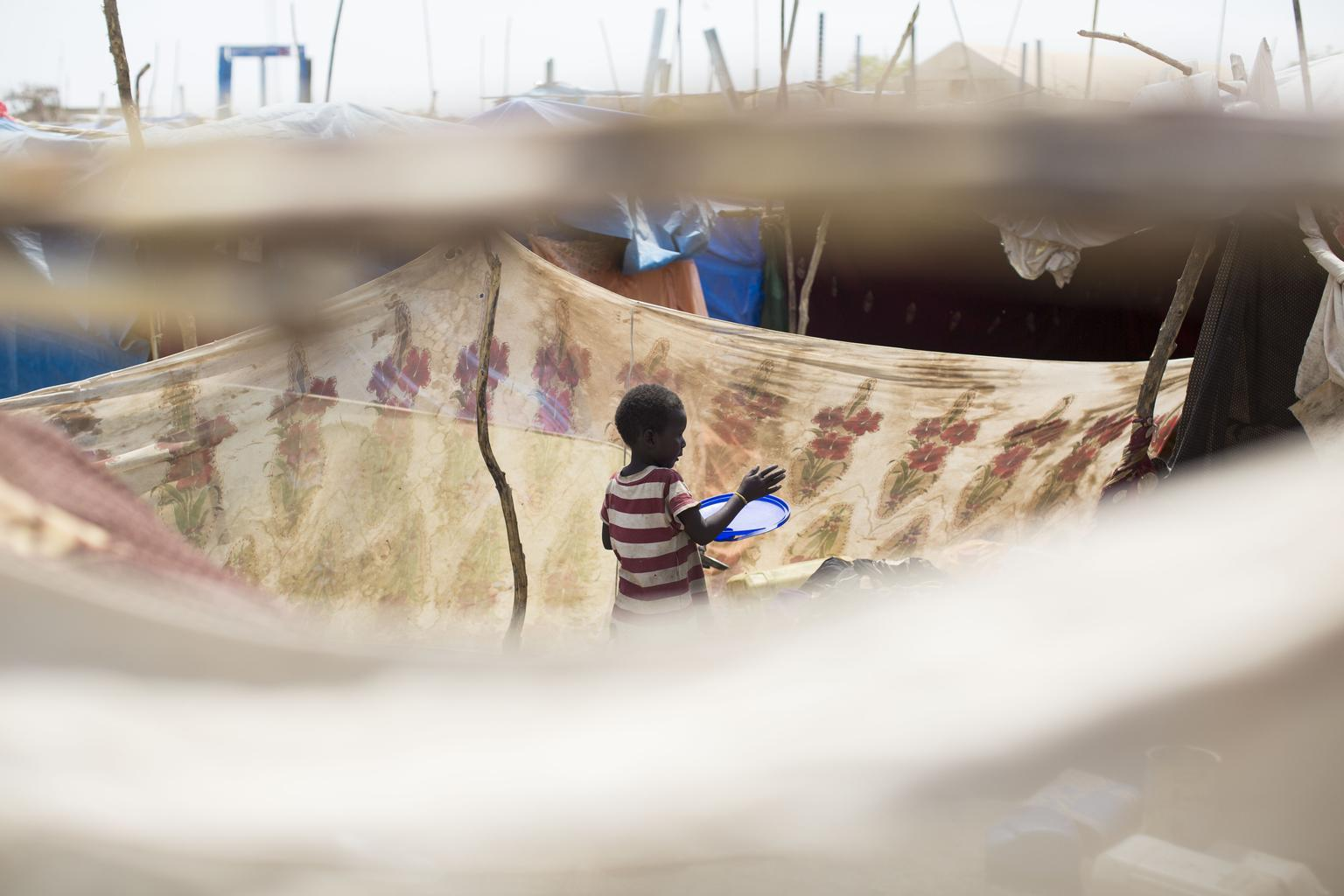 A girl stands inside the tent where she and her family now live in a camp for displaced people, located on the base of the United Nations peacekeeping mission in South Sudan, in the city of Malakal.