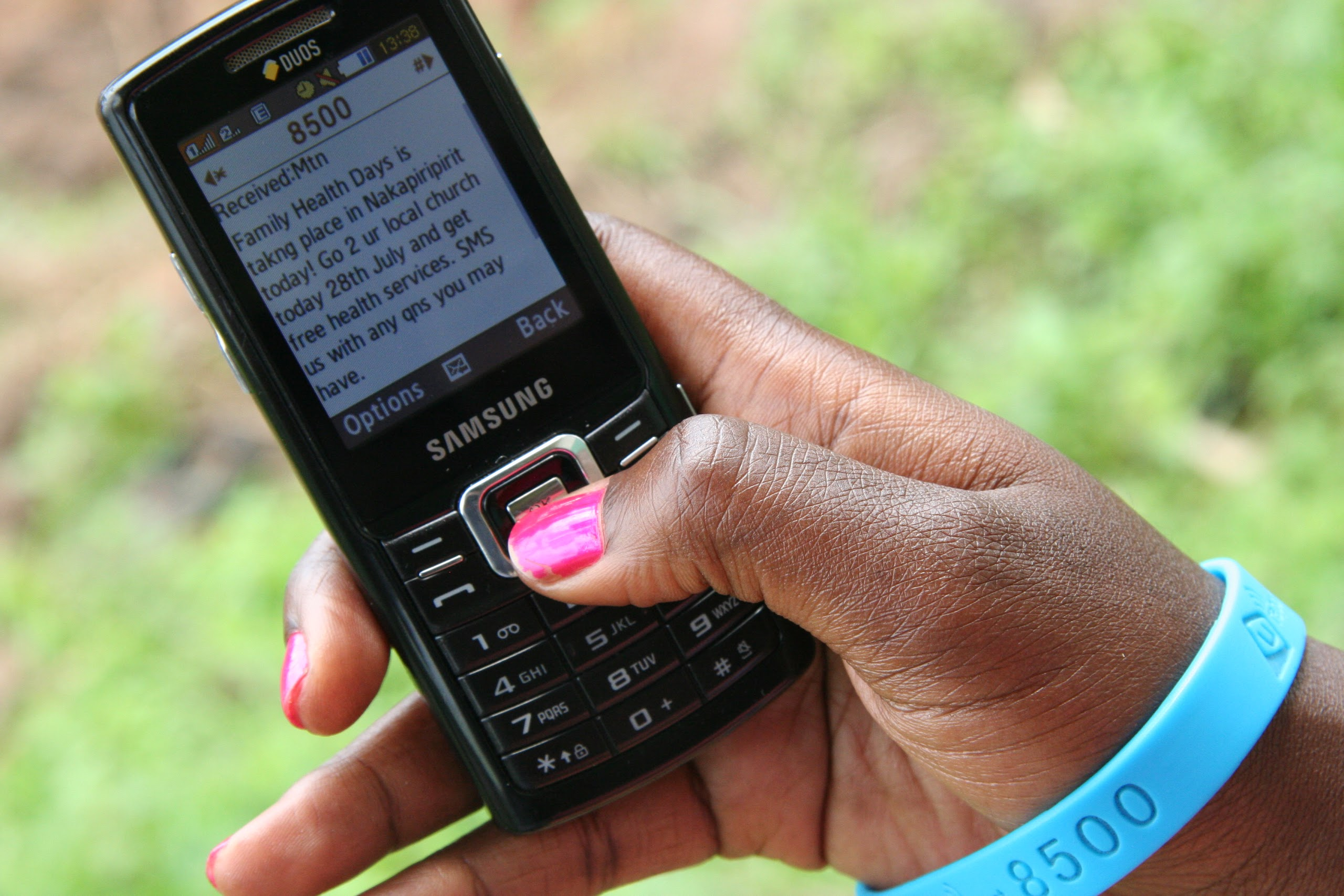 A young woman holds up a mobile phone displaying a U-report message.