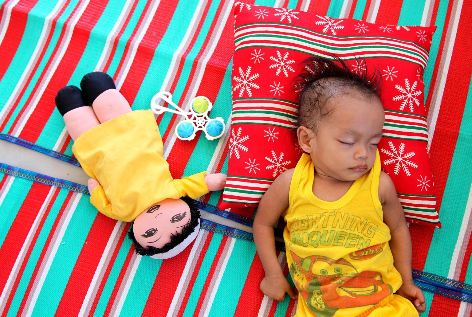 A few months after Typhoon Haiyan, a young child sleeps in a parent/baby-friendly tent, in the city of Tacloban. Numerous risk factors - such as poor nutrition and exposure to violence - can impact on a child's brain development during the early years of life.