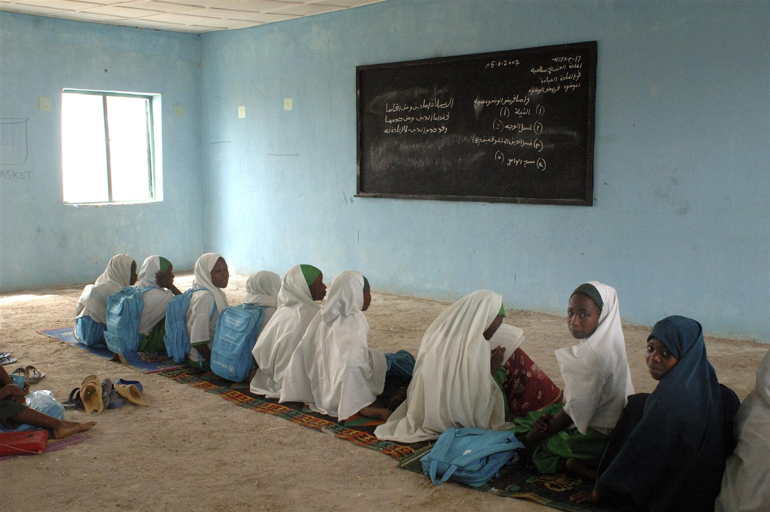 Girls sit on the floor of their classroom, in Nigeria