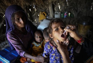 A child receives a dose of oral polio vaccine in Pakistan.