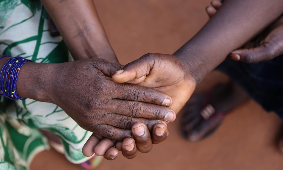 A child formerly associated with armed forces or groups in Central African Republic holds her mother's hand.