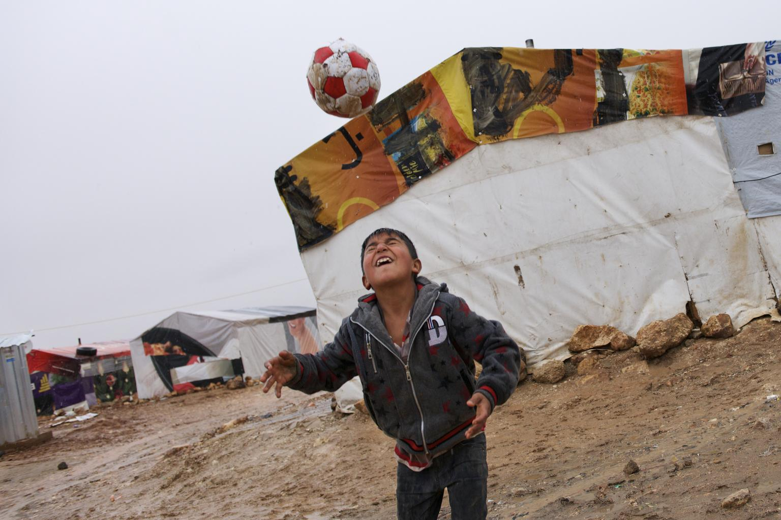 Hamid, from Syrian, plays with a football outside his family's tent shelter, in the Tal Al Abiad informal settlement in Baalbek, Lebanon.