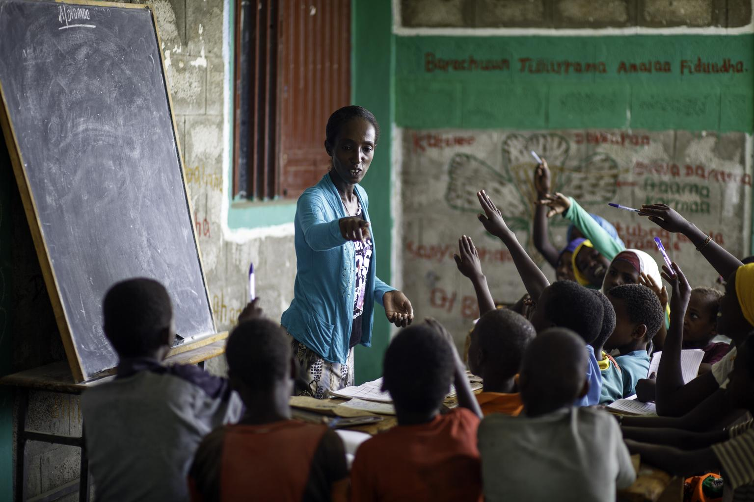 A teacher in Ethiopia conducts her class outside due to a lack of classrooms.