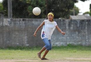 A girl plays football in a schoolyard in the city of Olinda in Brazil.