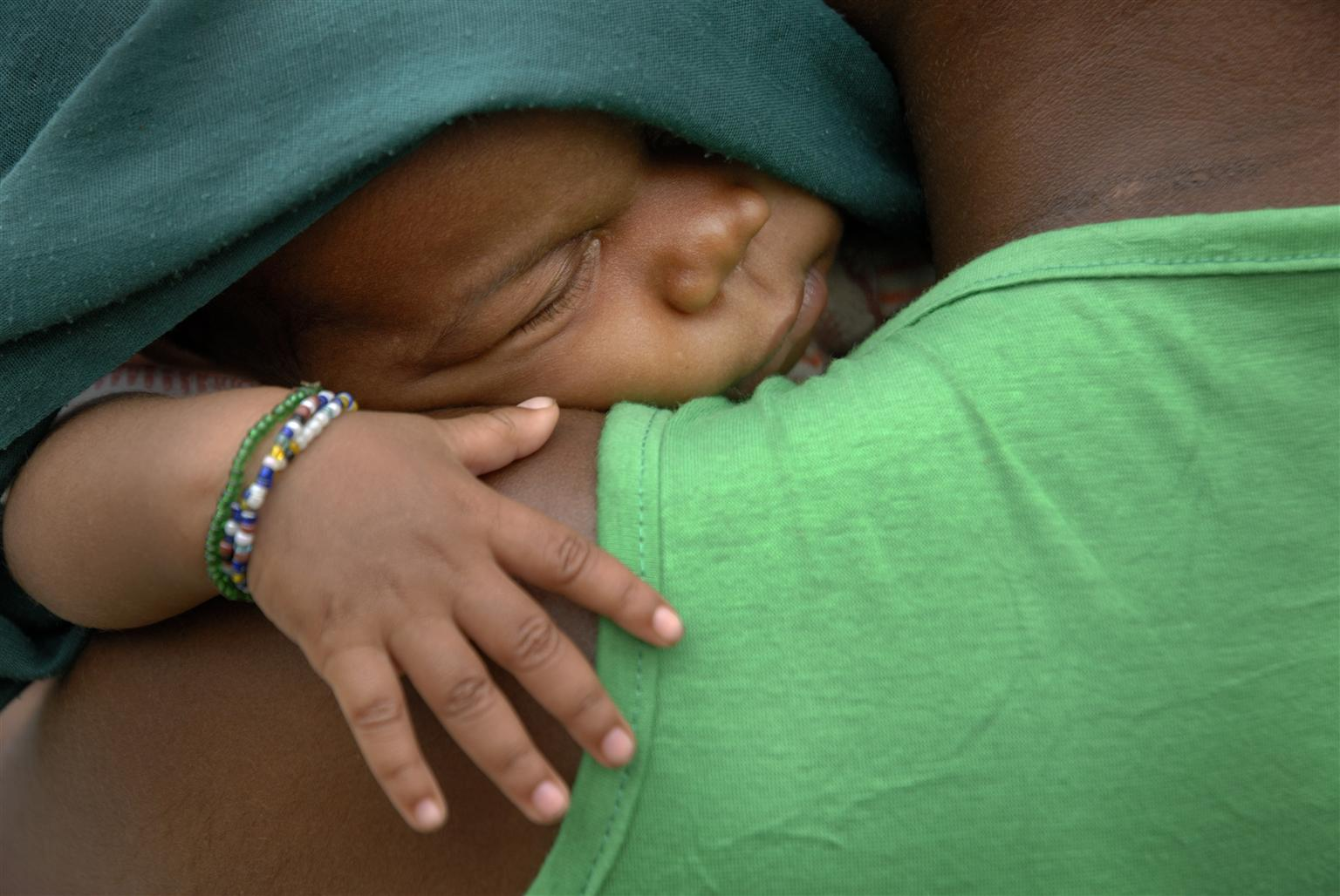 A woman from the indigenous Baka settlement holds her sleeping baby. © UNICEF/NYHQ2009-2528/Williams