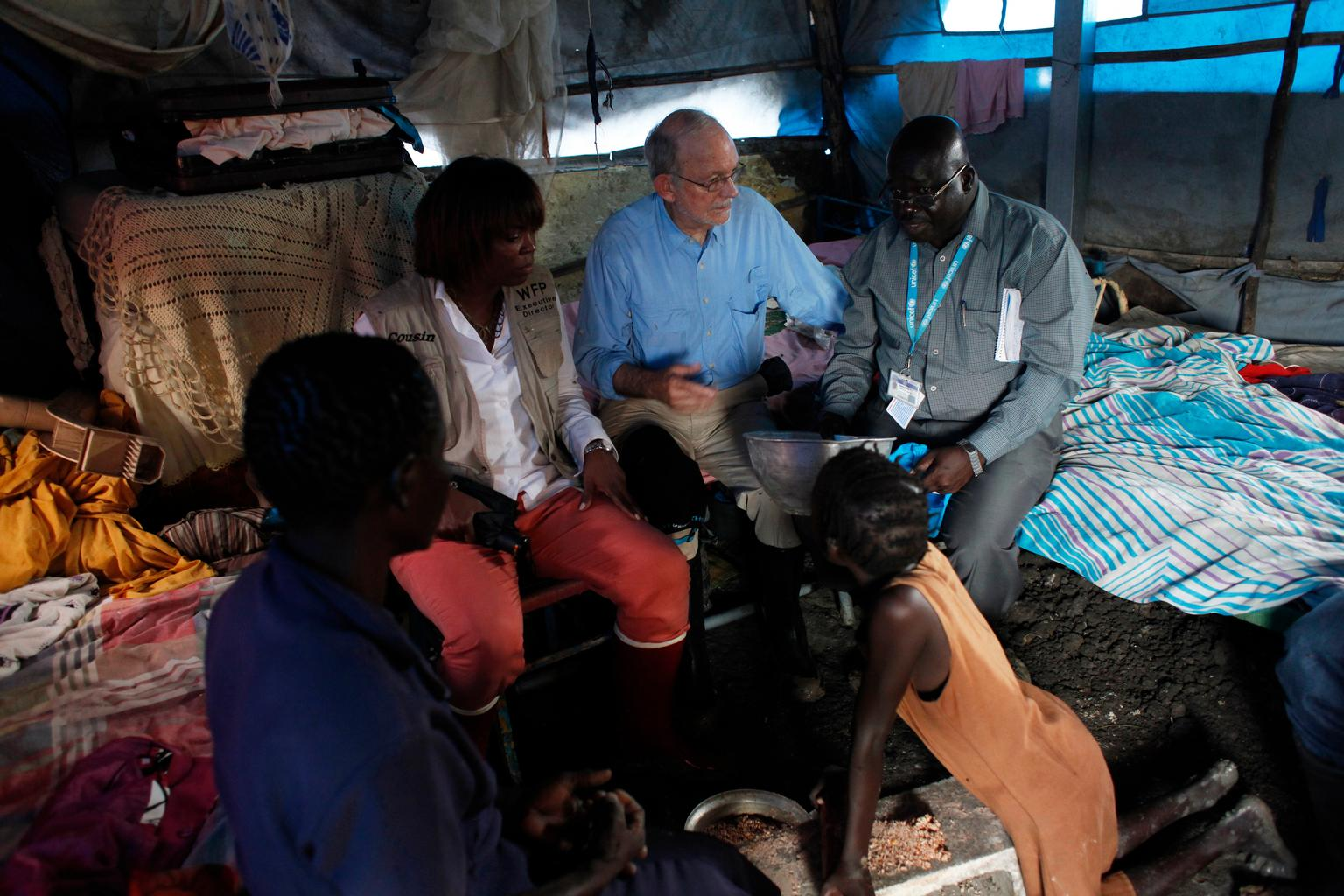 (Background, left to right) WFP's Executive Director Ertharin Cousin, UNICEF Executive Director Anthony Lake and a UNICEF worker meet with a woman and girl in their temporary shelter, at a UN camp in Malakal. © UNICEF/NYHQ2014-0985/WFP Campeanu