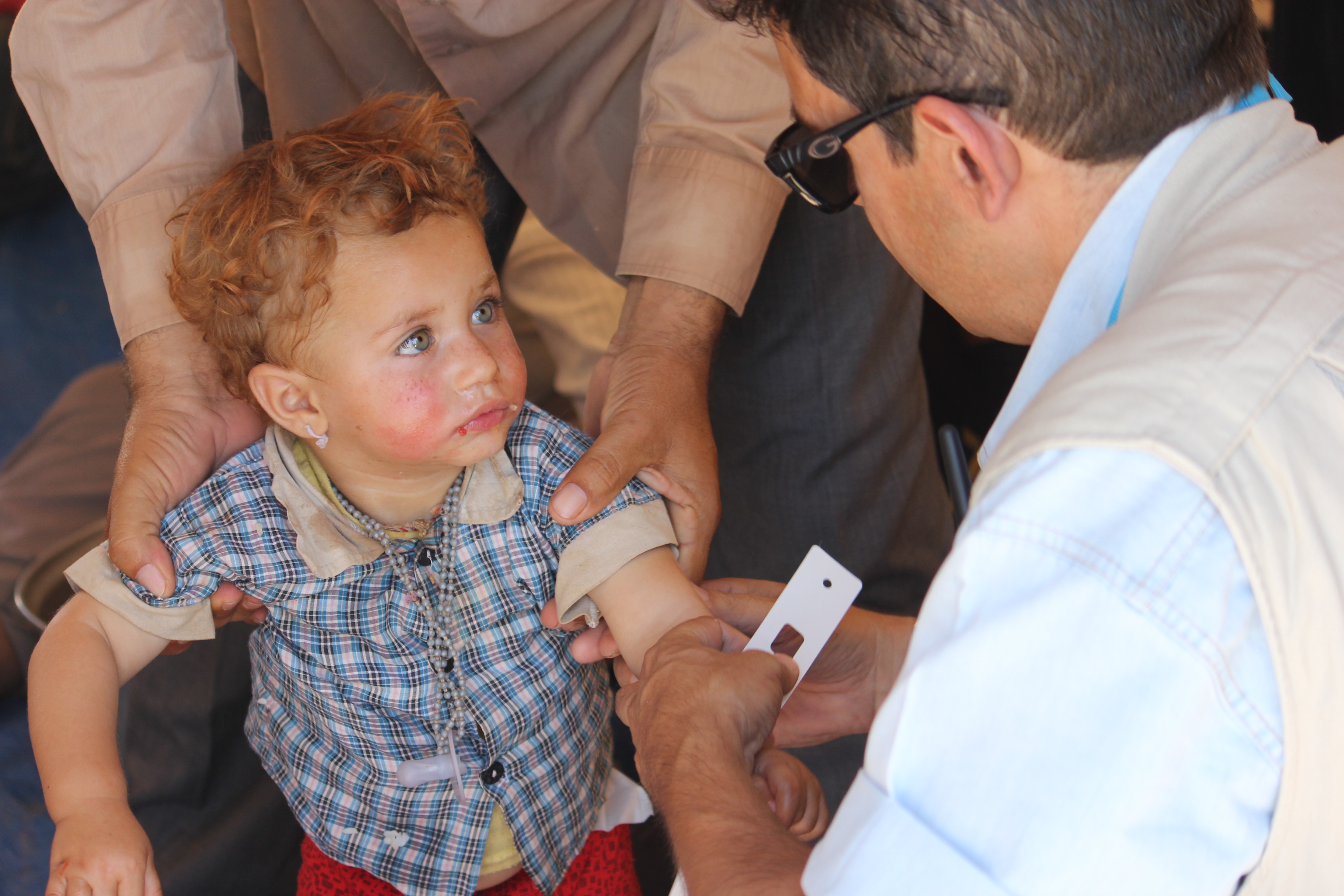 A UNICEF health worker at Nawrouz refugee camp in north-eastern Syria measures the arm of a young Yazidi child as part of a nutrition assessment. © UNICEF Syria/2014/Razan Rashidi