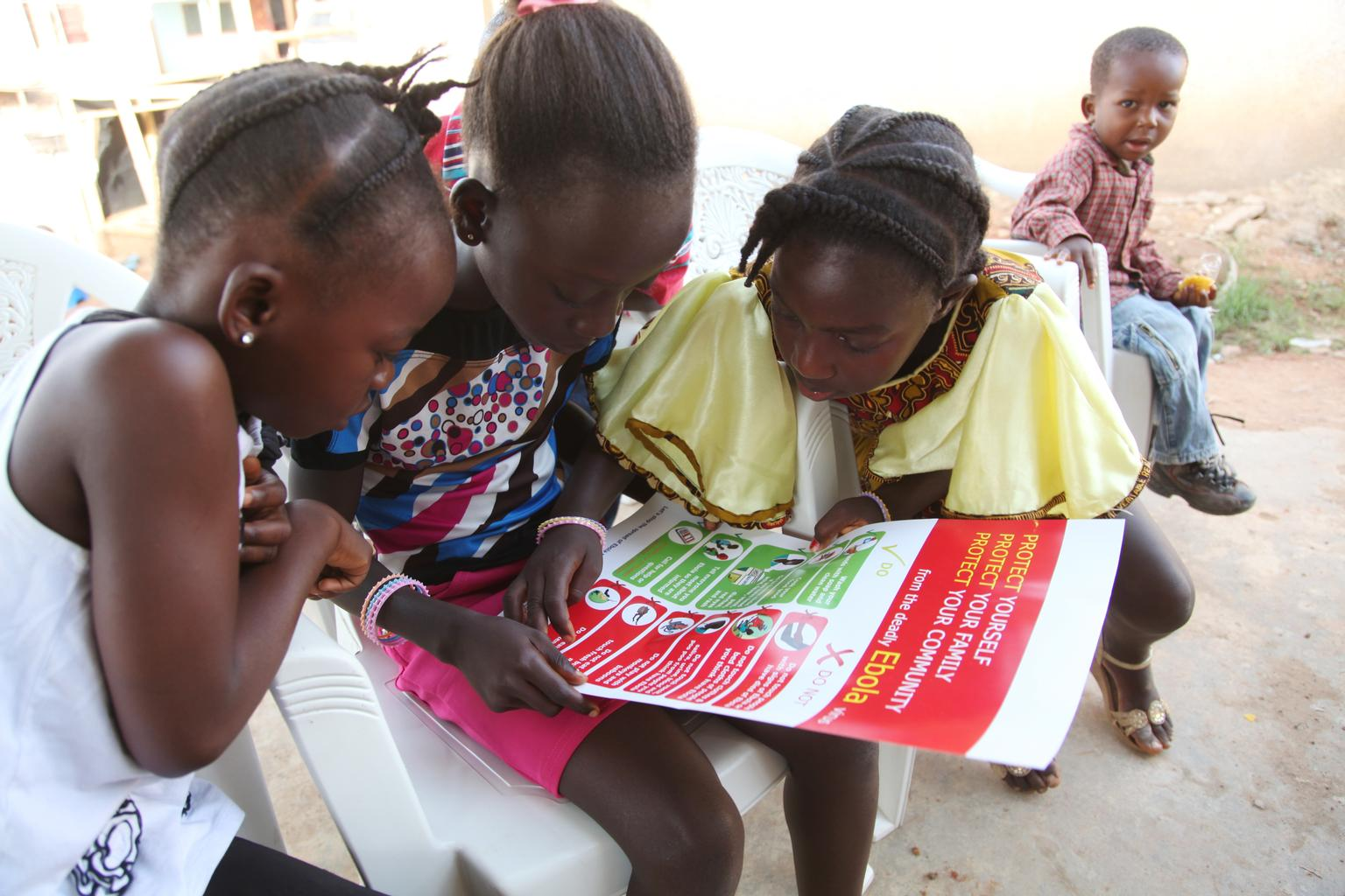 A group of girls in Liberia reads a poster with Ebola-prevention information.