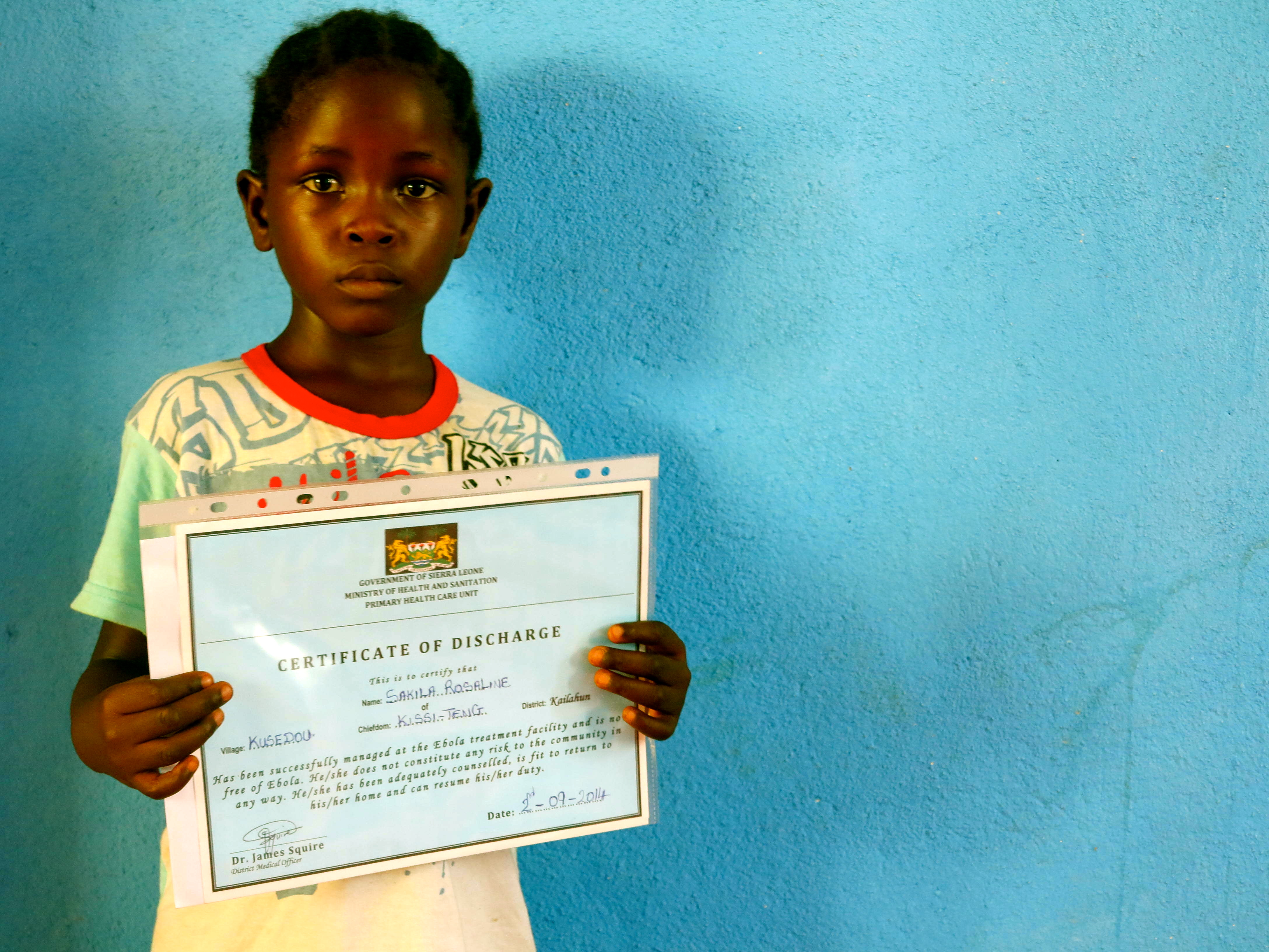 Rose shows off her certificate of good health that was issued to her by the Ministry of Health and Sanitation when she left the Ebola treatment centre. (c) UNICEF Sierra Leone/2014/Dunlop