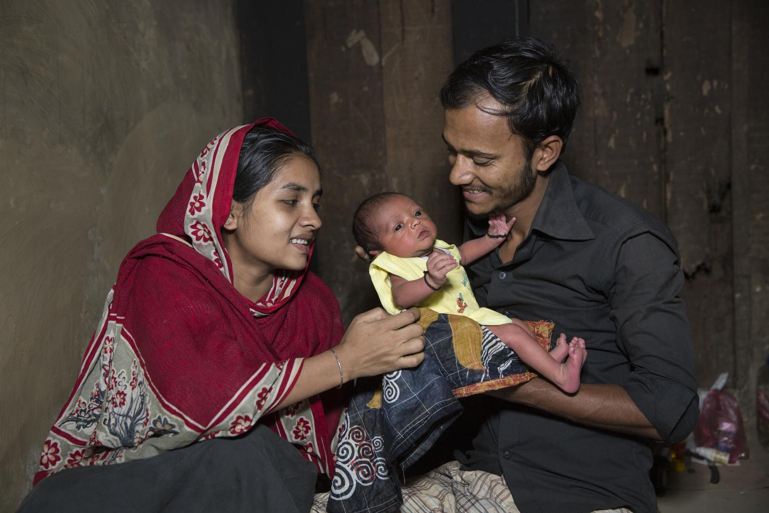 A couple in Bangladesh attend to their newborn child.