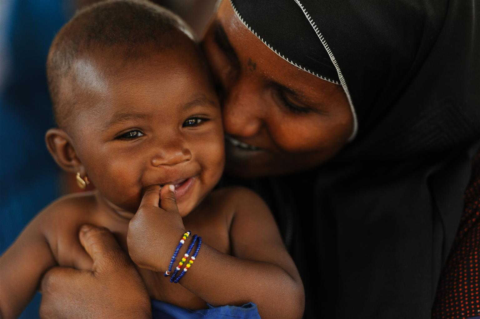 Six-month-old Maniratou, held by her mother, Habsatou Salou, smiles after a nutrition screening at a health centre in Niamey, Niger.