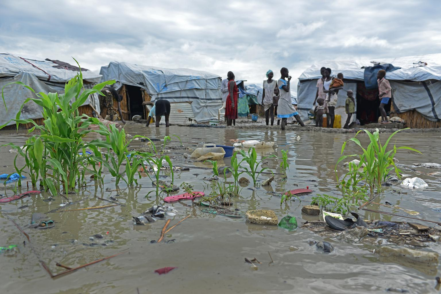 Displaced women and children stand in floodwaters outside shelters, near inundated plants and floating garbage, at the Bentiu Protection of Civilians (PoC) site, South Sudan.