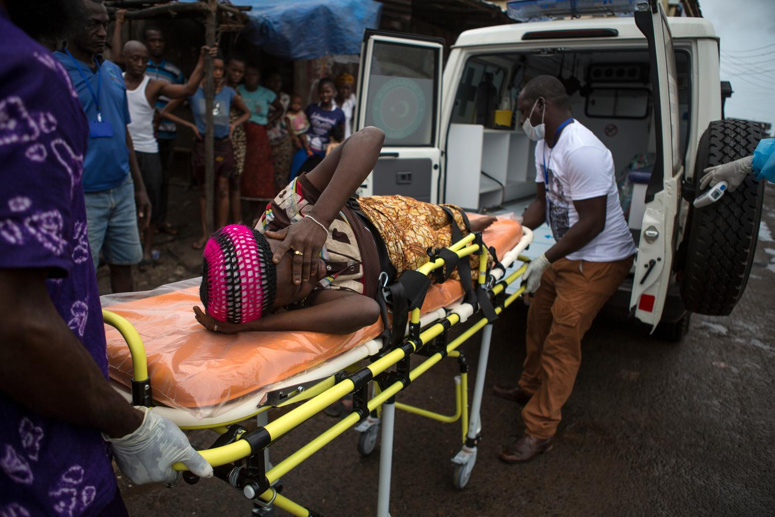 A woman, who is pregnant and suspected of having EVD, lies on a stretcher as health workers lift her into an ambulance. Nearby, people watch from a distance, afraid of getting too close to her.  © UNICEF/NYHQ2014-1580/Bindra