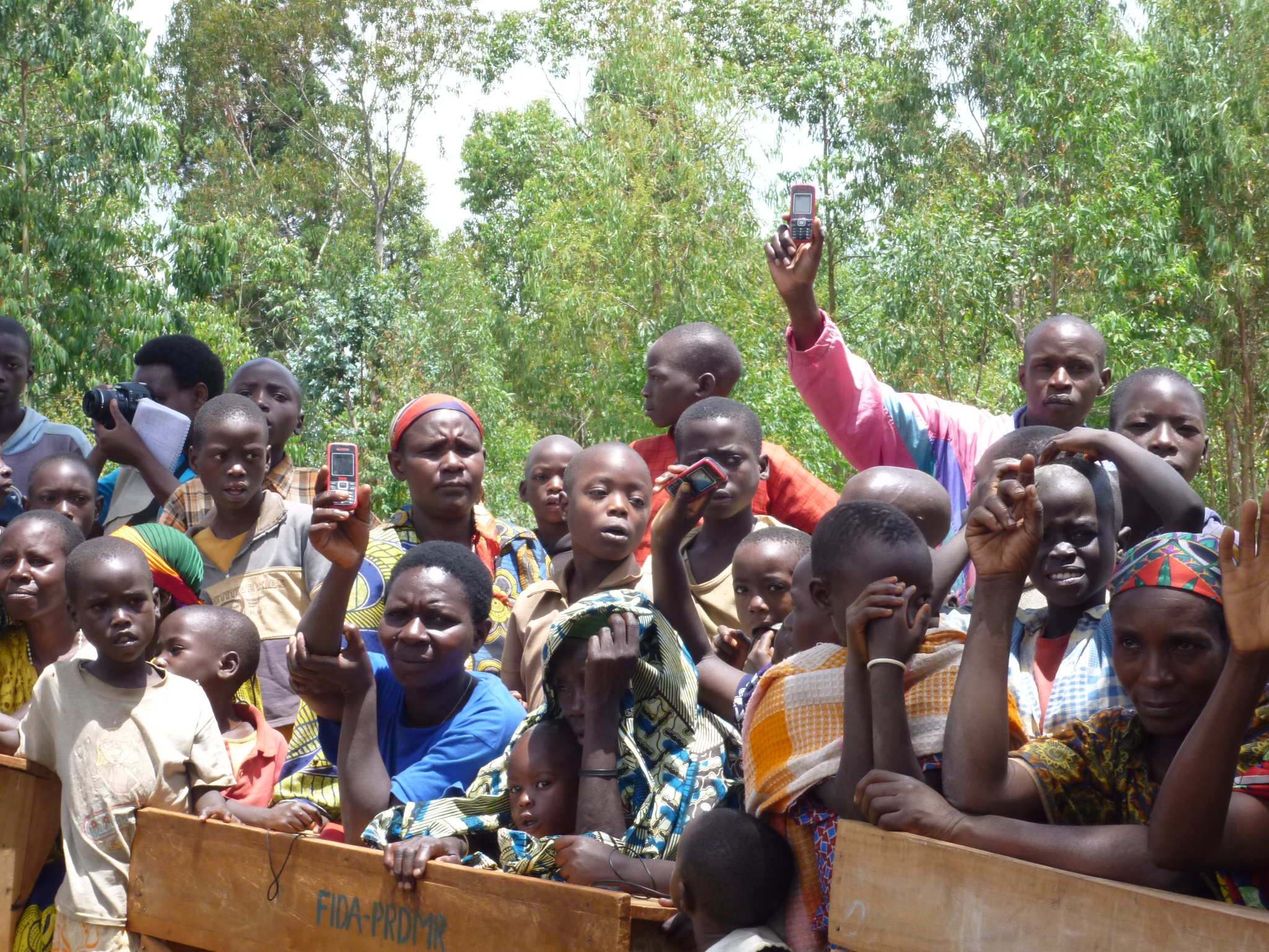 On a colline in Burundi, people hold up their mobile phones
